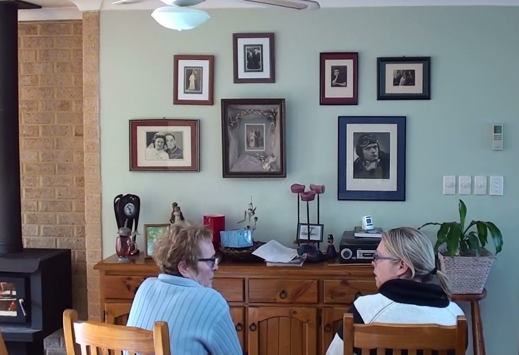 Figure 3: Hanna and Alex, sitting in front of family history wall, 2016, digital image.